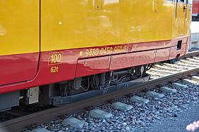 Das Foto zeigt den Wagenkasten einer rot-gelb lackierten Stadtbahn. Die Räder befinden sich auf der Schiene. Darunter befinden sich graue Schottersteine.