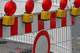 rot-weiße Absperr-Schranke mit Baustellen-Lichtern