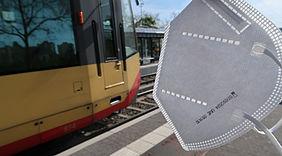 In der rechten Bildhälfte ist eine weiße FFP2-Mske zu sehen. Links davon fährt eine rot-gelbe Stadtbahn in eine Haltestelle ein.