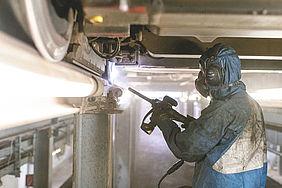 Ein Miitarbeiter einer Fachfirma steht in einem Schutzanzug unter einer aufgebockten Stadtbahn und reinigt die verklebten Radreifen mit Trockeneis.