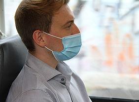 Junger Mann mit medizinischer Maske in der Bahn.