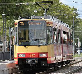 Eine gelb-rote Stadtbahn der AVG hält an einer Haltestelle. Im Hintergrund sind grüne Bäume zu sehen.