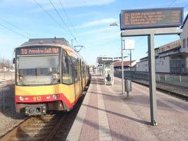 Eine gelb-rote Stadtbahn der AVG steht auf einem Gleis an der Haltestelle Freudenstadt Stadt. Rechts von der Bahn befindet sich der Bahnsteig mit einem Fahrgaszanzeiger, Mülleimer und Wartehäuschen. Der Himmel ist hellblau und leicht bewölkt.