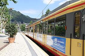 Rechts im Bild befindet sich eine AVG-Stadtbahn an einer Haltestelle in Bad Wildbad. Links ist der Bahnsteig zu sehen. Im Hintergrund befinden sich grüne, bewaldete Hügel des Schwarzwaldes.