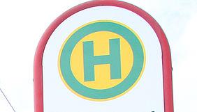 Rot umrandetes haltestellen-Schild mit eimem grünen Buchstaben H.